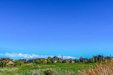 Vast grassy terrain with houses under blue sky and puffy clouds on a sunny day