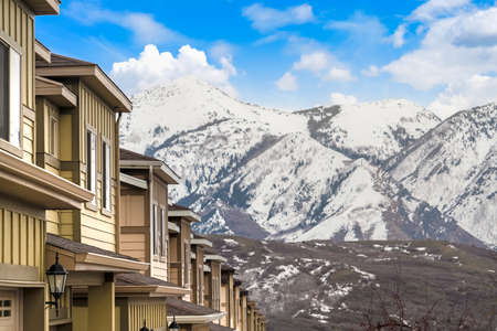 Row of houses with view of a mountain blanketed with snow in winter 스톡 콘텐츠