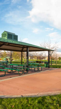 Vertical Covered picnic area on a scenic park under cloudy blue sky