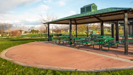 Panorama frame Covered picnic area on a scenic park under cloudy blue sky