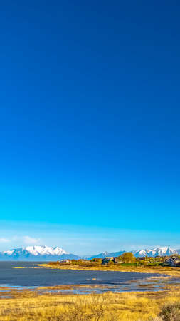 Vertical frame Panoramic view of a lake and snow covered mountain under deep blue sky 스톡 콘텐츠