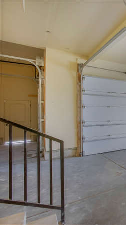 Vertical Empty garage with white doors as well as arched and rectangular windows