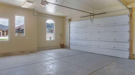 Panoramarahmen Leere Garage mit weißen Türen sowie Rundbogen- und Rechteckfenstern Standard-Bild