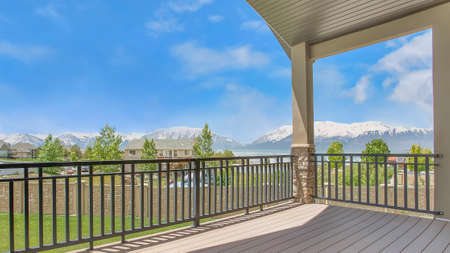 Panorama frame Balcony overlooking homes lake and mountain under blue sky on a sunny day 스톡 콘텐츠