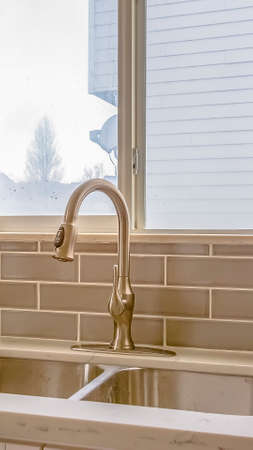 Vertical Double sink and faucet of a kitchen with view of outdoors through the window Stock Photo