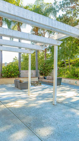 Vertical Patio with a white wooden pergola attached to the wall of the home Stock Photo