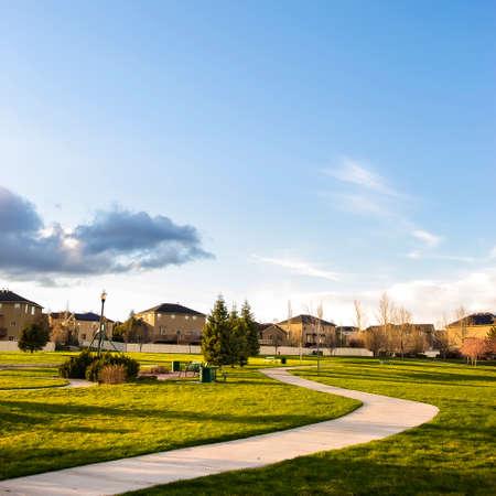 Campo quadrato lussureggiante con un percorso curvo che conduce alle case in lontananza Archivio Fotografico