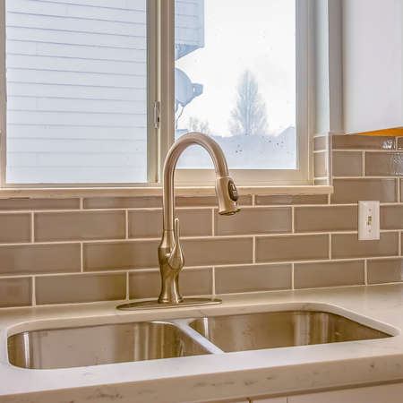 Square frame Double sink and faucet of a kitchen with view of outdoors through the window Stock Photo - 124947342