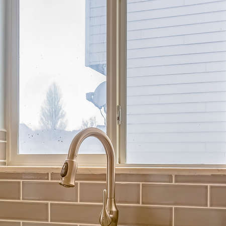 Square Double sink and faucet of a kitchen with view of outdoors through the window Stock Photo - 124947344