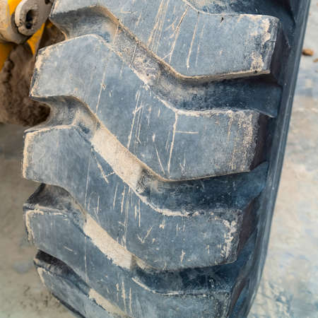 Square frame Close up view of the huge qnd dirty black tire of a loader Imagens