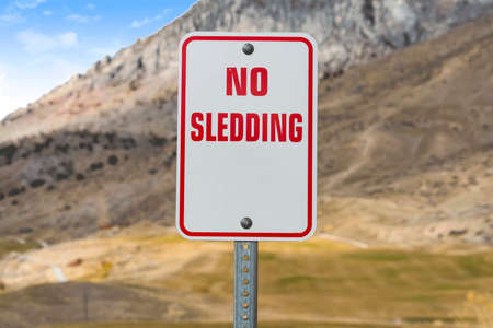 Close up of a No Sledding sign with a towering mountain in the background Stock Photo