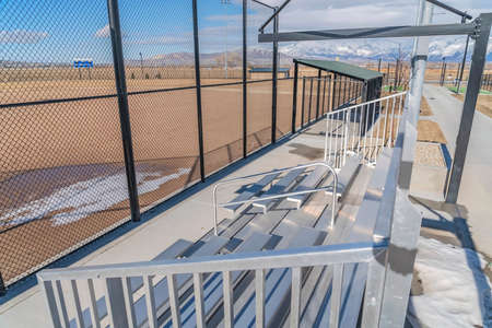 Bleachers behind the fence of a baseball field with melting snow on the ground. The seats also has a view of distant snow capped mountain against cloudy sky.