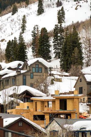 Homes and coniferous trees on a mountain covered with snow in winter. A home under construction can also be seen on this frosty landscape. 스톡 콘텐츠