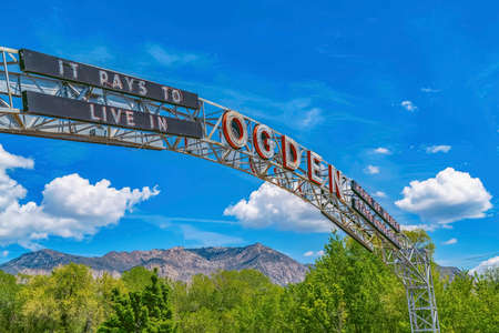 The welcome arch in Ogden Utah against vibrant trees and towering mountain. Vast blue sky with puffy clouds can also be seen in the background on this sunny day.