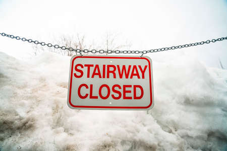 Close up of sign that reads Stairway Closed against snow covered slope in winter. The white and red sign is hanging on a metal chain. Standard-Bild - 126968439