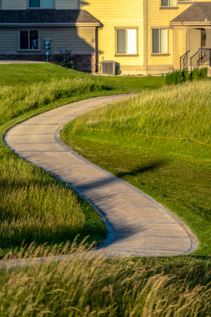 Pathway that winds through a grassy terrain with houses in the background. The landscape is illuminated by sunlight on this sunny day.