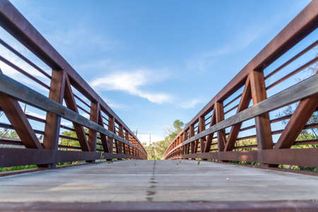 Wooden deck and rusty guardrails of a bridge against blue sky on a sunny day. Lush trees and grasses can also be seen from the structure.
