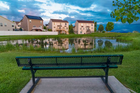 Green metal bench facing a shiny pond with reflection of homes and cloudy sky. Vivid green grasses and trees grow in the expansive terrain.