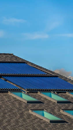 Vertical frame Pitched roof with solar water heater solar panels and skylights. Light blue sky with clouds can be seen in the background on this sunny day.