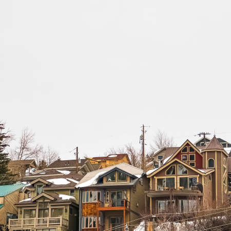 Square Hill homes with balconies and snowy roofs against cloudy sky in winter