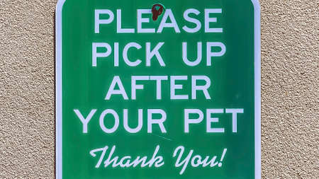 Panorama frame Sign that reads Please Pick Up After Your Pet against a concrete wall surface
