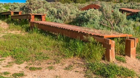Panorama frame Elevated wooden bike tracks amid bushes and grasses on a hill under blue sky