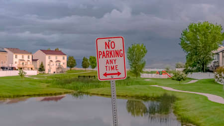 Panorama frame No Parking At Any Time sign with pond grassy terrain and homes in the background