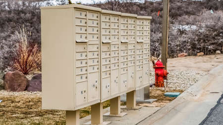 Panorama White metal cluster mailboxes and red fire hydrant along a concrete road