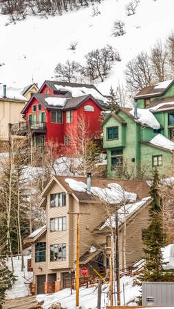 Vertical Homes built on the slope of a mountain blanketed with snow during winter Stock fotó