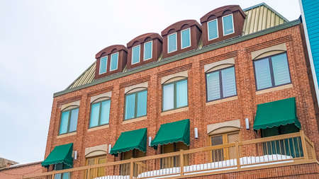 Panorama Exterior of a red brick building with green awnings on the balcony windows