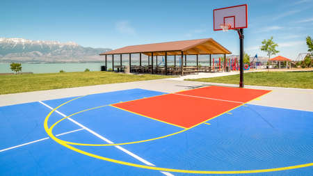 frame Outdoor basketball court with a picnic pavilion and playground in the background
