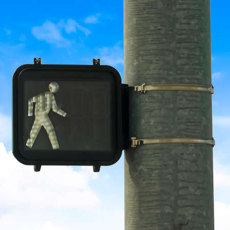 frame Close up of pedestrian traffic light signal against blue sky and bright clouds