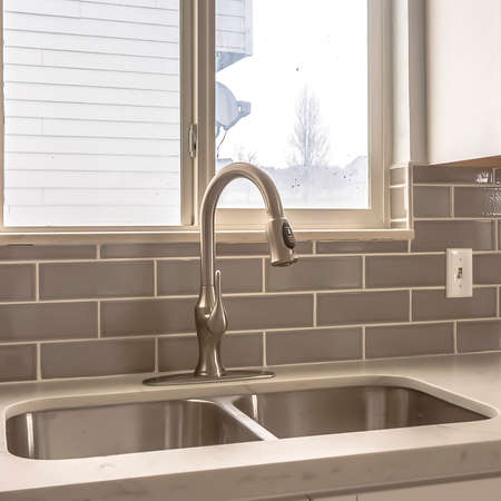 Square Polished kitchen countertop with double basin stainless steel sink and faucet