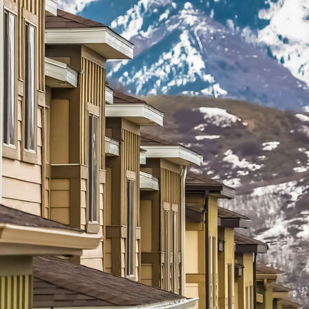 Square Close up of upper storey of homes against snow blanketed mountain in winter