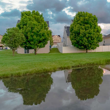 Square frame Homes and trees reflected on the shiny water of a pond amid a grassy terrain Фото со стока