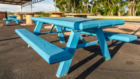 Blue picnic tables with seats and spool tables under a pavilion on a sunny day