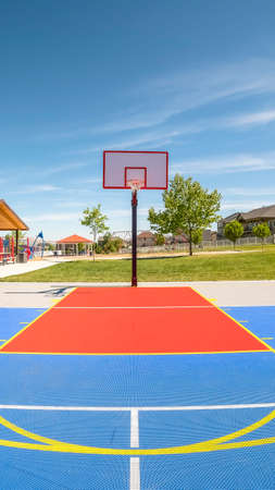 Vertical frame Outdoor basketball court at a park with picnic pavilion and childrens playground