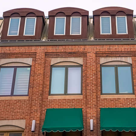 Square frame Exterior view of a building with red brick wall and green awnings on the windows Фото со стока