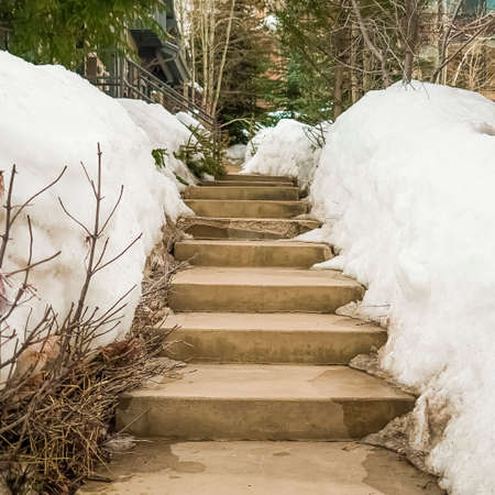 Square frame Weathered concerete outdoor steps amid snow covered slope in winter
