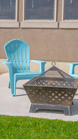 Vertical Square fire pit and blue plastic chairs on the yard of a home on a sunny day
