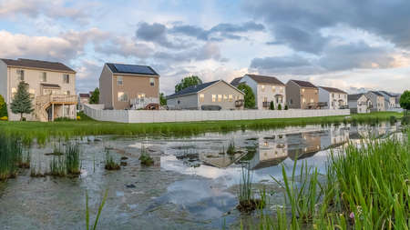 Panorama Beautiful multi storey homes built in front of a grassy and shiny pond Фото со стока