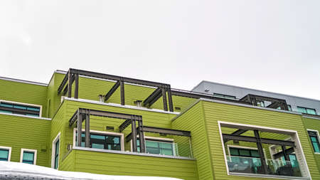 Panorama frame Building with green horizontal siding and balconies with glass railings