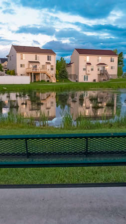 Vertical Vertical Green metal bench facing a shiny pond with reflection of homes and cloudy sky