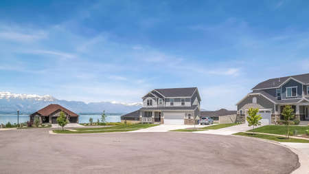 Panorama Peaceful neighborhood with scenic view of lake and mountain under blue sky. Driveways, lawns, and porches can be seen at the facade of the homes.