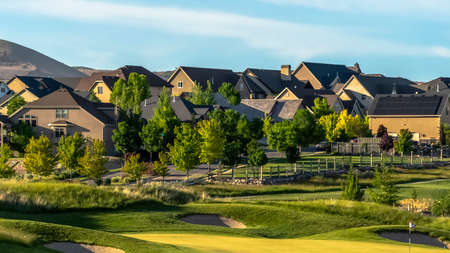 Panorama frame Scenic neighborhood with golf course lovely homes and abundant trees. A mountain and blue sky can also be seen on this sunny landscape.