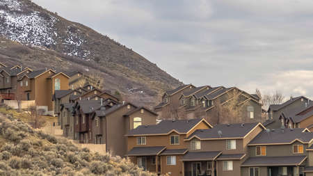 Panorama Rows of houses built on a mountain slope with view of cloudy sky overhead. A bit of powdery snow can be seen near top of the mountain.