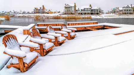 Panorama frame Adirondack wooden chairs on a deck overlooking lake and houses in winter. The seats and lake deck are covered with fresh white snow.