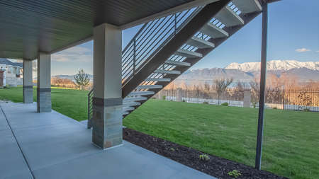 Panorama frame Home porch under a wooden brown ceiling supported by rectangular pillars. The stairs that leads to the upper floor has a view of the yard and snow capped mountain.