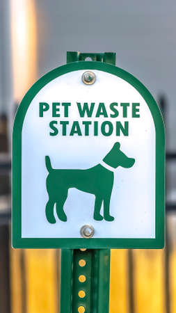 Vertical frame Close up of a Pet Waste Station with gate and building in the blurry background