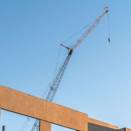 Quadratisches Gebäude im Bau mit Metallkran und Hintergrund des blauen Himmels